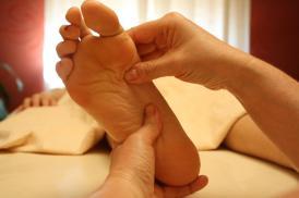 Hände massieren einen Fuß
