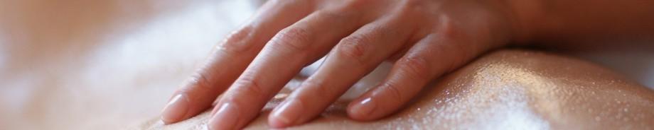 Massagehand liegt auf eingeölter Haut