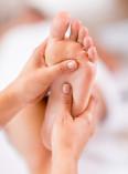 Fußreflexzonentherapie am linken Fuß mit Therapeutenhänden