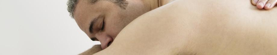 Mann entspannt in Bauchlage bei Rückenmassage